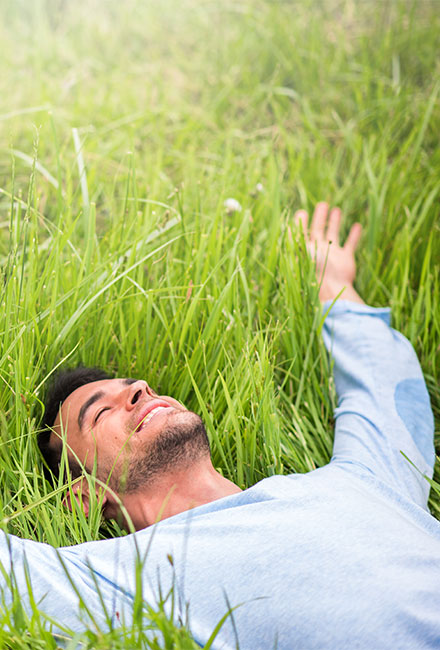 young man lying in  a green field